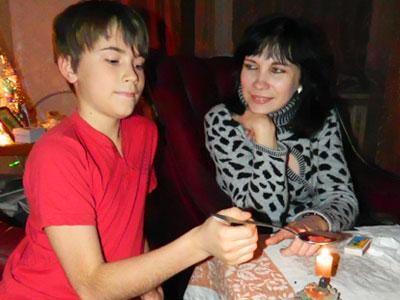 Марина Шажко показывает своему выросшему крестнику, как много лет назад его «нагадали».