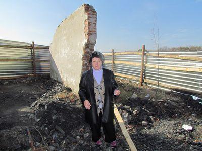 Валентина Брыкова (она живет в поселке, работает на шахте, активно борется  с «нелегалами») стоит на фоне той самой «ожидаловки», которую продали за шахтные долги.